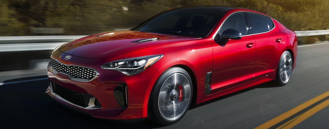 A red 2021 Kia Stinger is driving on an empty highway.