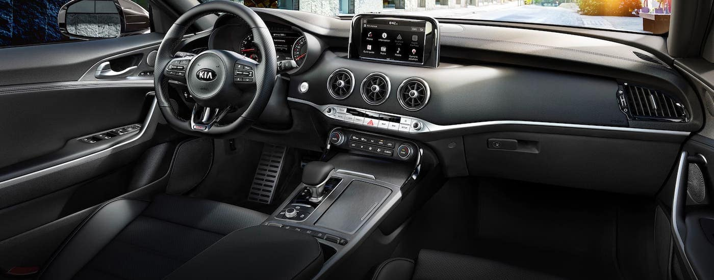 The black interior and front seats of a 2021 Kia Stinger are shown.