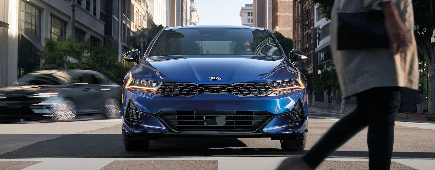 A blue 2021 Kia K5 is parked at a crosswalk after leaving the Kia Dealership in Lakewood NJ.