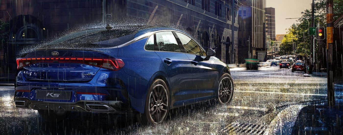 A blue 2021 Kia K5 is parked in the rain.