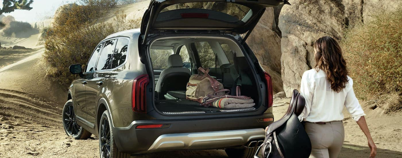 A tan 2021 Kia Telluride is parked in the desert with a woman loading equestrian gear into the hatch.
