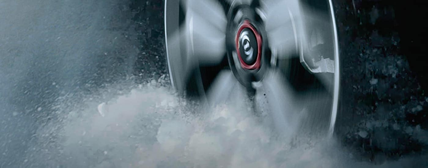 The close up of a wheel on a 2021 Kia Seltos is spinning in the snow.