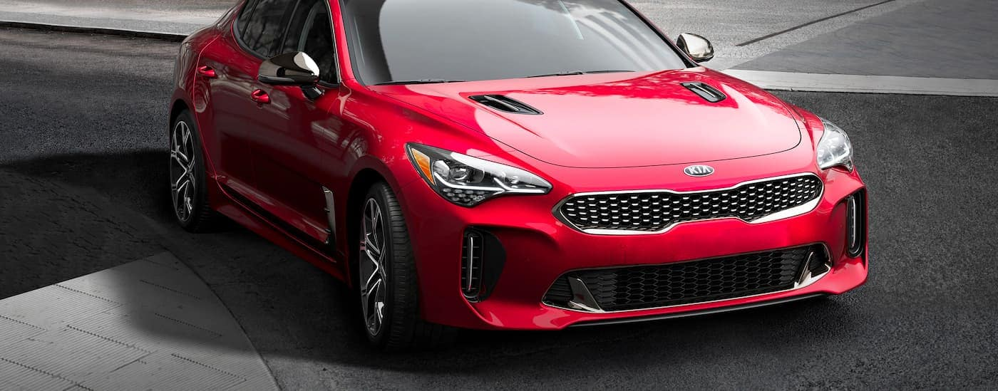 A red 2021 Kia Stinger is parked on asphalt after leaving a Kia Dealership in NJ.