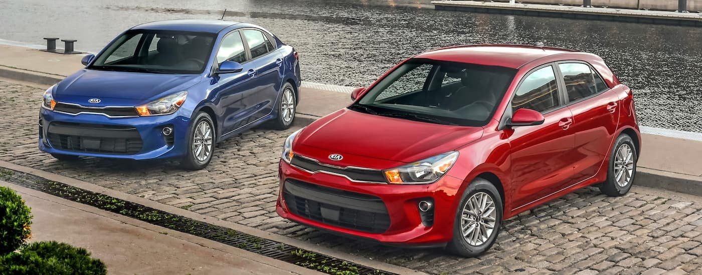 A popular Kia car model, a red hatchback and a blue sedan 2020 Kia Rio, are parked on a brick path by a river.