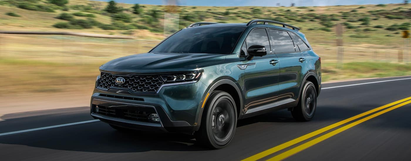 A dark green 2021 Kia Sorento is driving down the highway after leaving the Kia dealership.