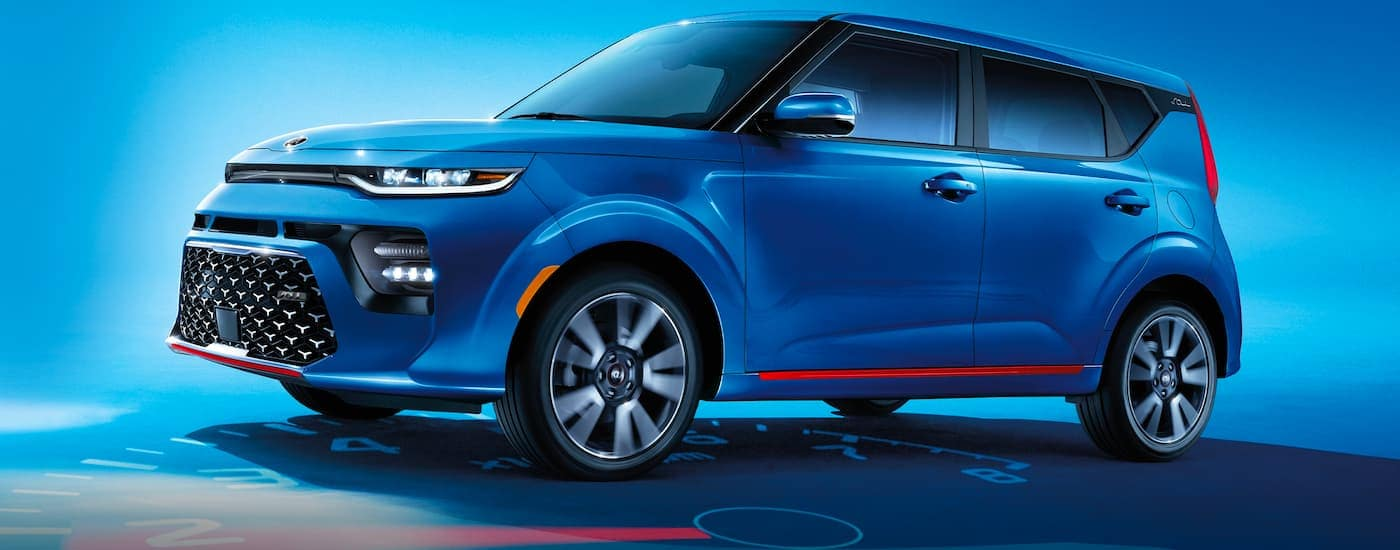 A blue 2021 Kia Soul is shown with a blue background parked on a tachometer.