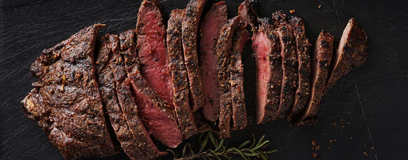 A medium rare steak is shown against a black background.