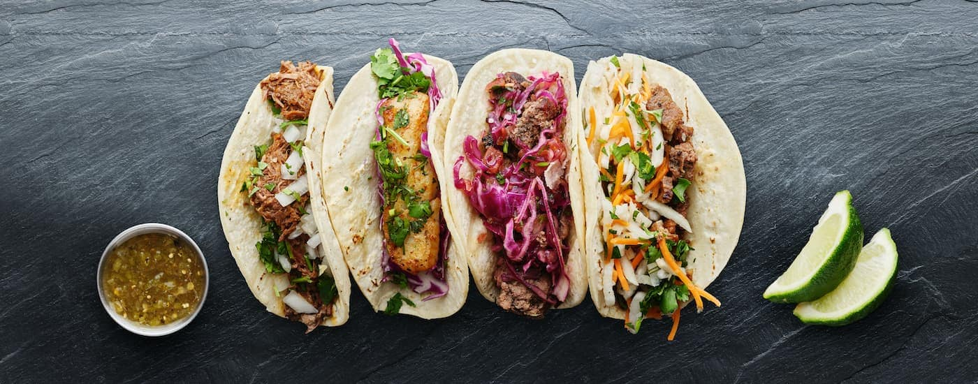Multiple tacos are shown from a high angle on a slate table.