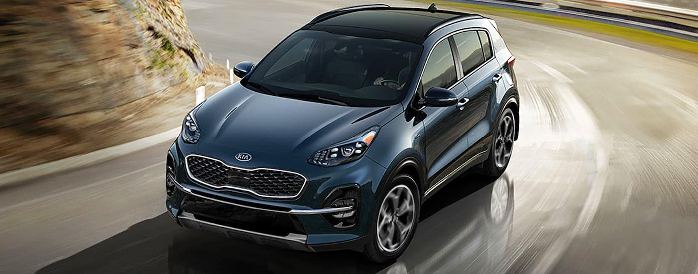 A blue 2020 Kia Sportage is driving on a winding road away from a city.