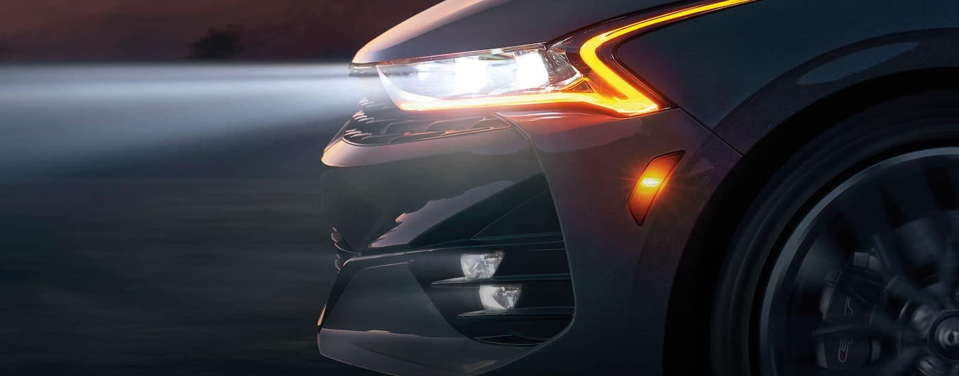 A closeup shows a headlight on a 2021 Kia K5 from the side at dusk.