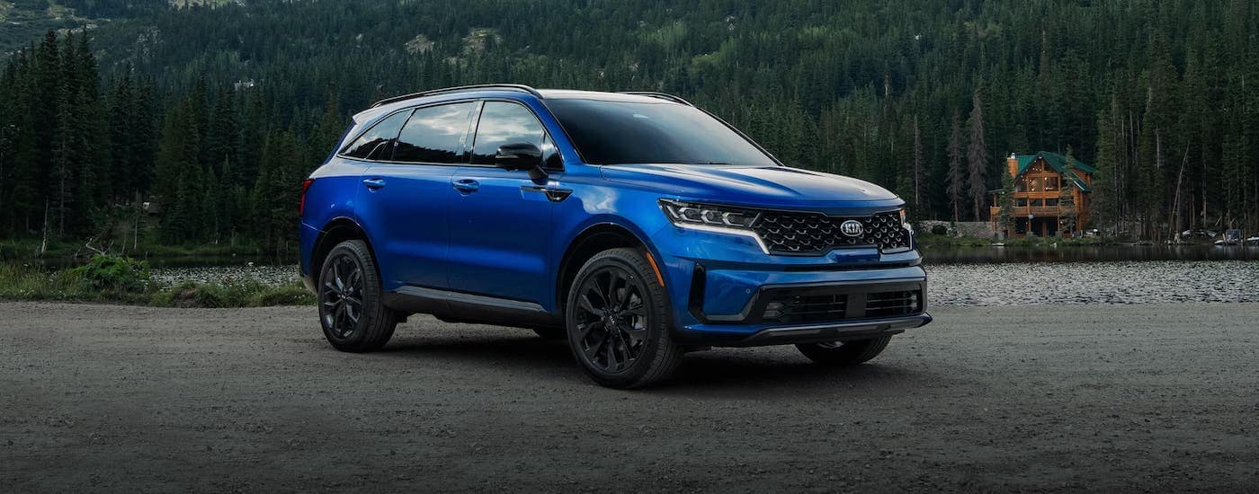 A blue 2021 Kia Sorento is parked in front of a lake and a cabin.