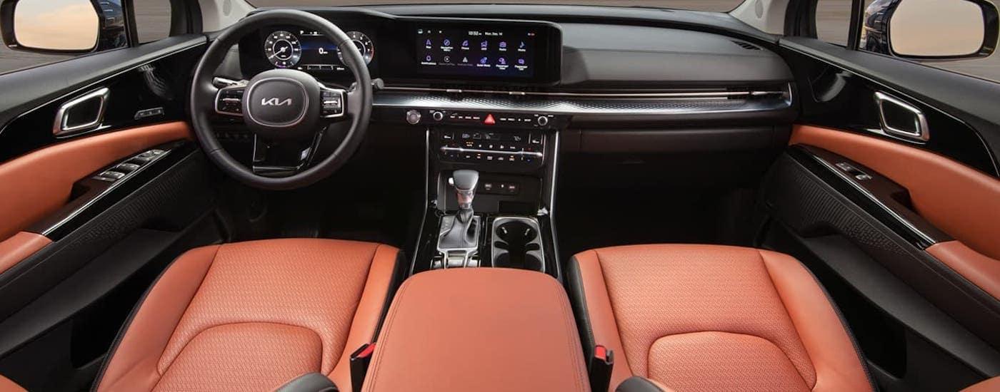 The orange seats and black dashboard are shown in a 2022 Kia Carnival.