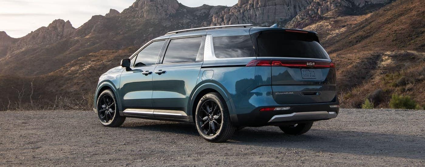 A blue 2022 Kia Carnival is overlooking mountains and shown from a rear three-quarter angle.