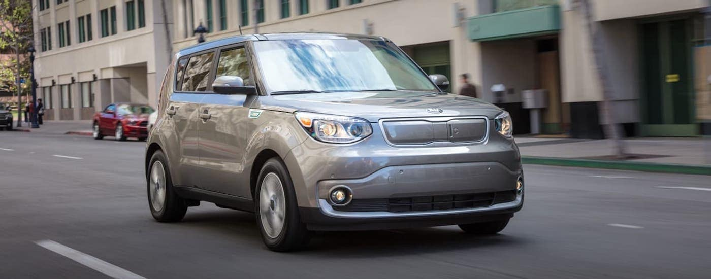 A silver 2019 Kia Soul EV is driving on a city street.