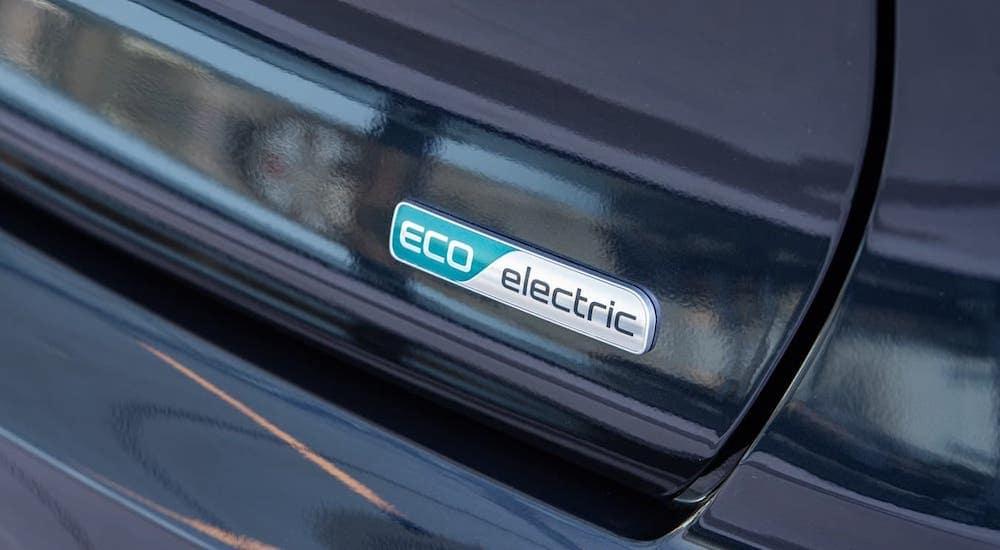 A closeup of the Eco Electric badge is shown on a black Kia EV, a 2020 Kia Niro EV.