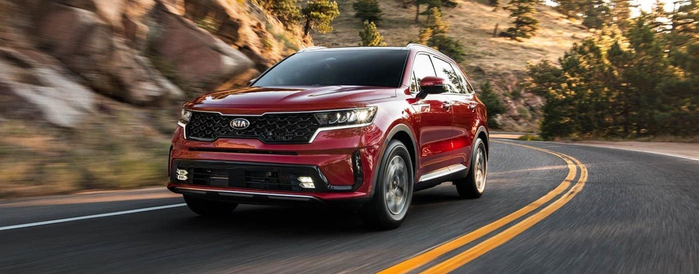 A red 2021 Kia Sorento HEV is driving next to a rock face.
