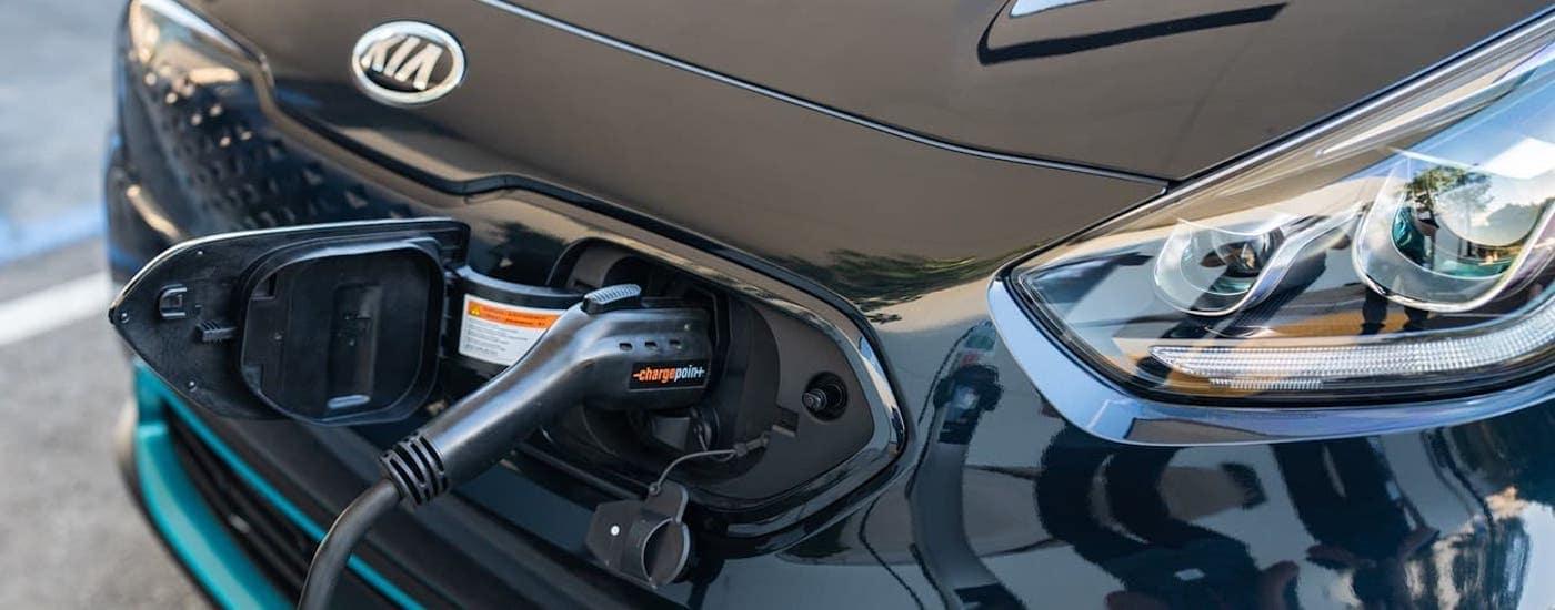 A closeup shows the charging port of a black 2020 Kia Niro EV.