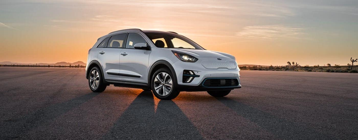 A silver 2020 Kia Niro, a popular Kia EV, is parked in an empty lot at sunset.
