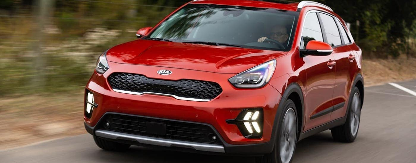 A red 2021 Kia Niro Hybrid is driving on a tree-lined road.