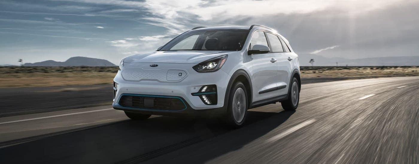 A white 2021 Kia Niro EV is driving on a desert highway.