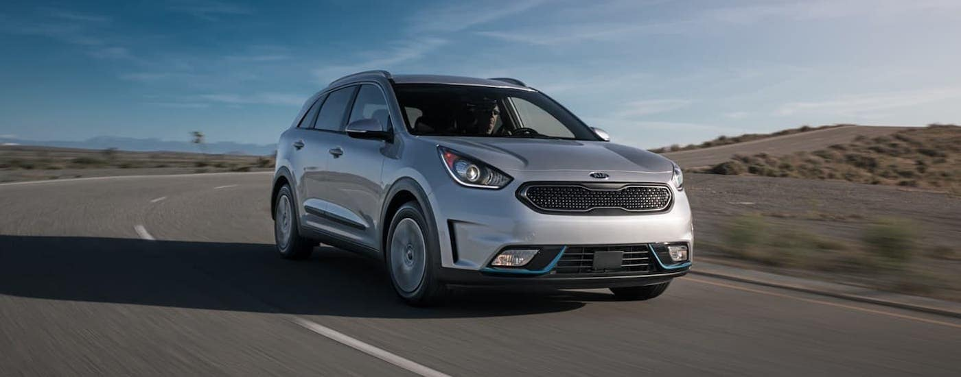 The perfect Kia hybrid, a silver 2021 Kia Niro PHEV, is driving on a desert highway.