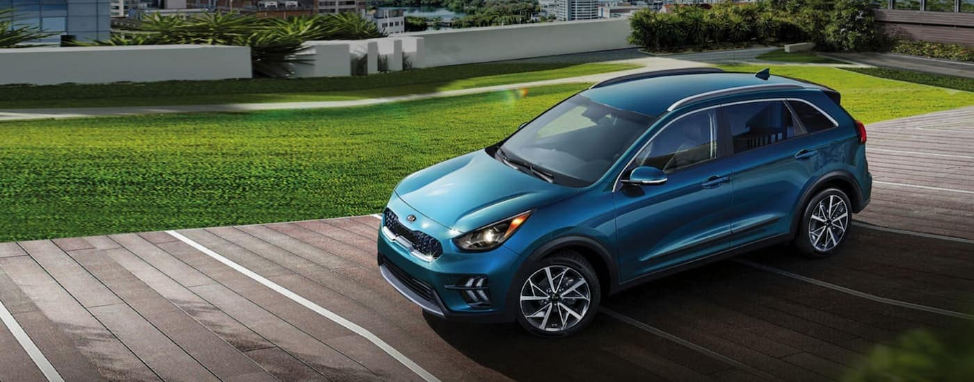 A blue 2021 Kia Niro, one of the Kia hybrids, is parked next to a green lawn.