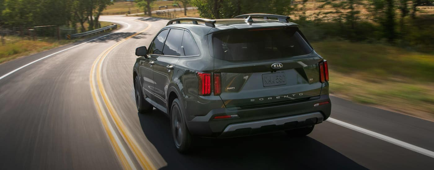 A green 2021 Kia Sorento is driving on a winding road toward a mountain range.