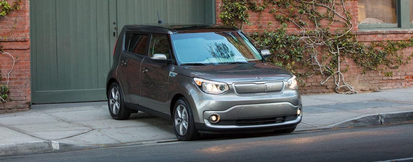 A gray 2019 Kia Soul is parked in front of a red brick building with vines.