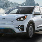 A white 2020 Kia Niro EV is driving down an open road in front of mountains.