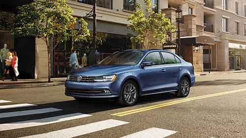 2018 Volkswagen Jetta driving down a downtown subaruban street