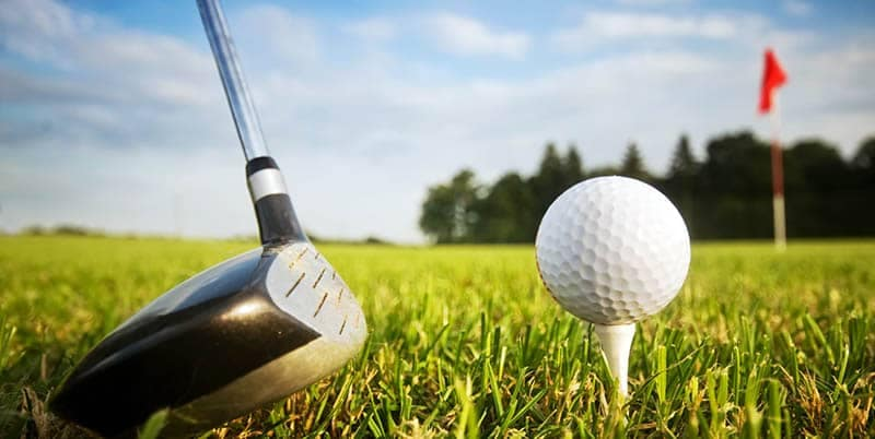 Golf course with close up of golf club and ball