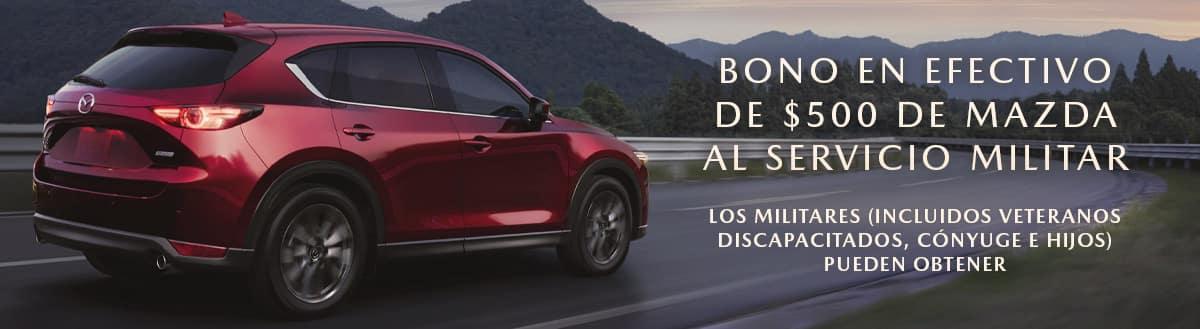 Red Mazda CX-5 on the left is driving into the sunset. The words 'BONO EN EFECTIVO DE $500 DE MAZDA AL SERVICIO MILITAR' and 'Los militares (incluidos veteranos discapacitados, cónyuge e hijos) pueden obtener' appears on the right. Sport Mazda Orlando, FL