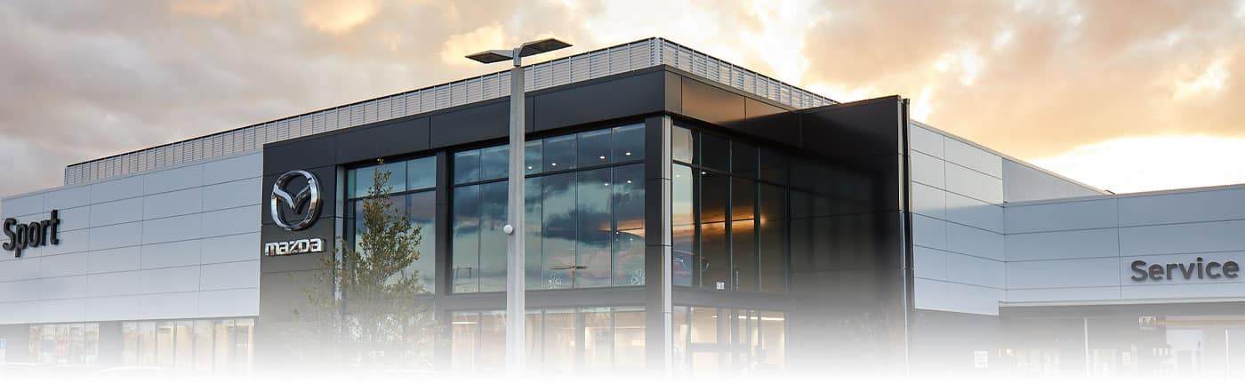 Sport Mazda dealership building in the evening.