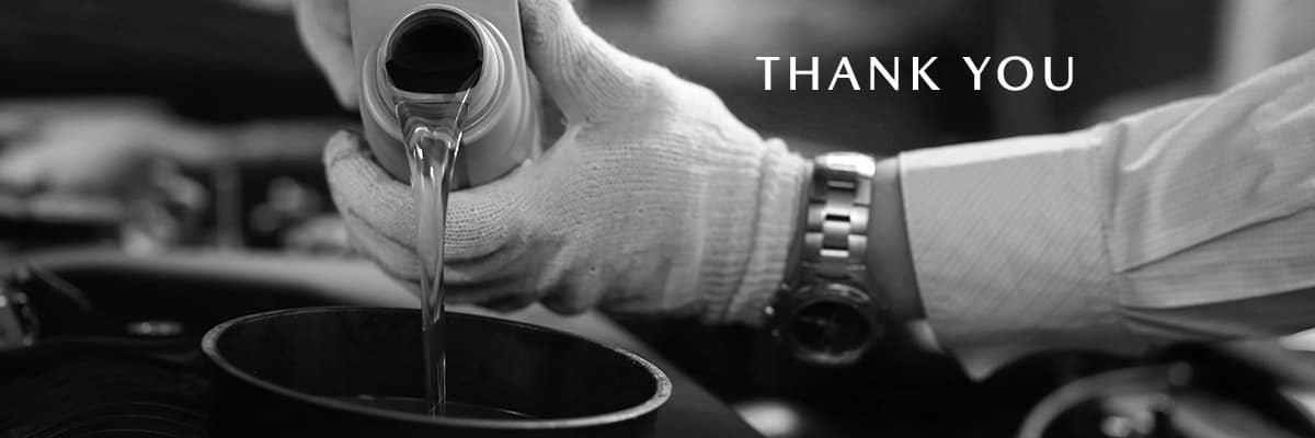 Black and white photo of oil being poured into an engine.