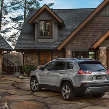 2019 Jeep Cherokee parked in front of large house