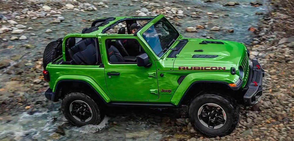 Green 2019 Jeep Wrangler driving over rocks and water