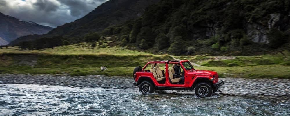 Jeep Wrangler with top off driving through stream in front of a mountain