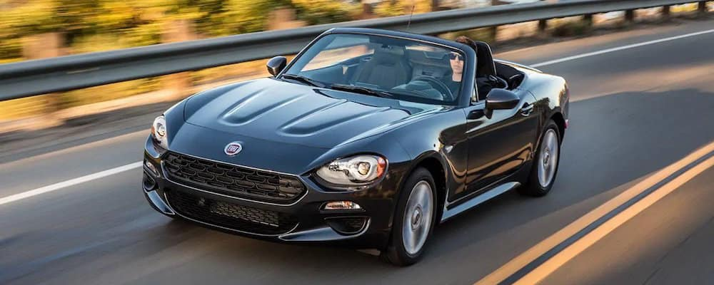Black 2019 FIAT 124 Spider driving on scenic highway