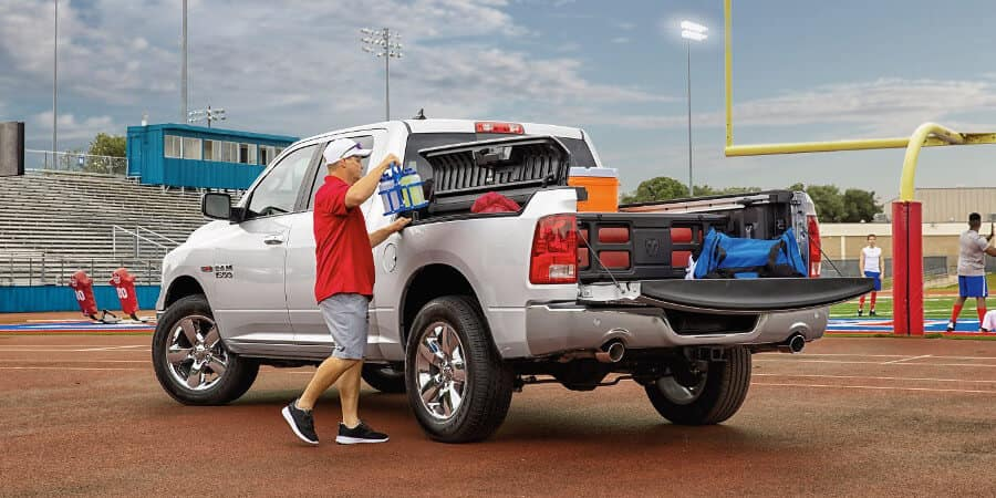 Man places sports equipment in RamBox and Truck Bed