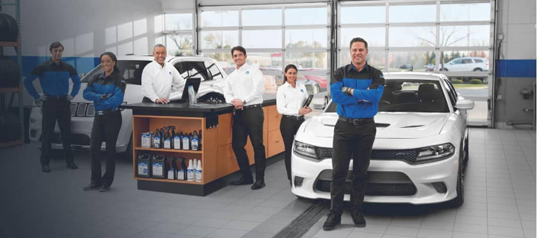 mopar service advisors stand in front of dodge challenger and jeep cherokee