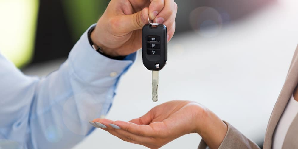 Dealer Handing Keys to Woman