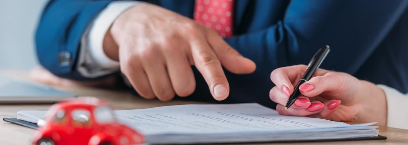 Man Pointing at Document Woman Signing
