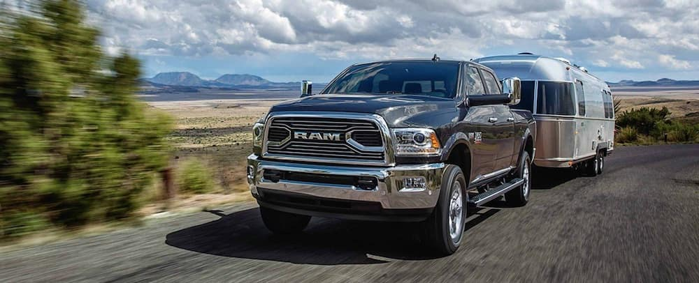 Black 2018 RAM 2500 heavy duty truck towing an airstream down a blacktop toad