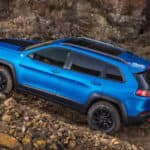 Blue Jeep Cherokee driving up mountain side