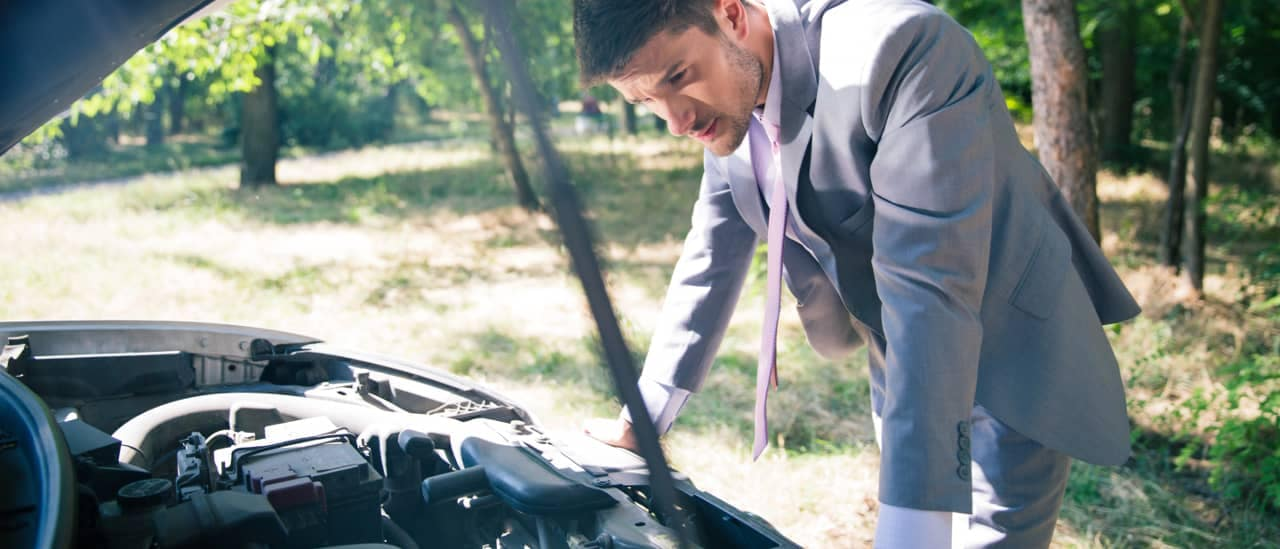 man looks under hood of car