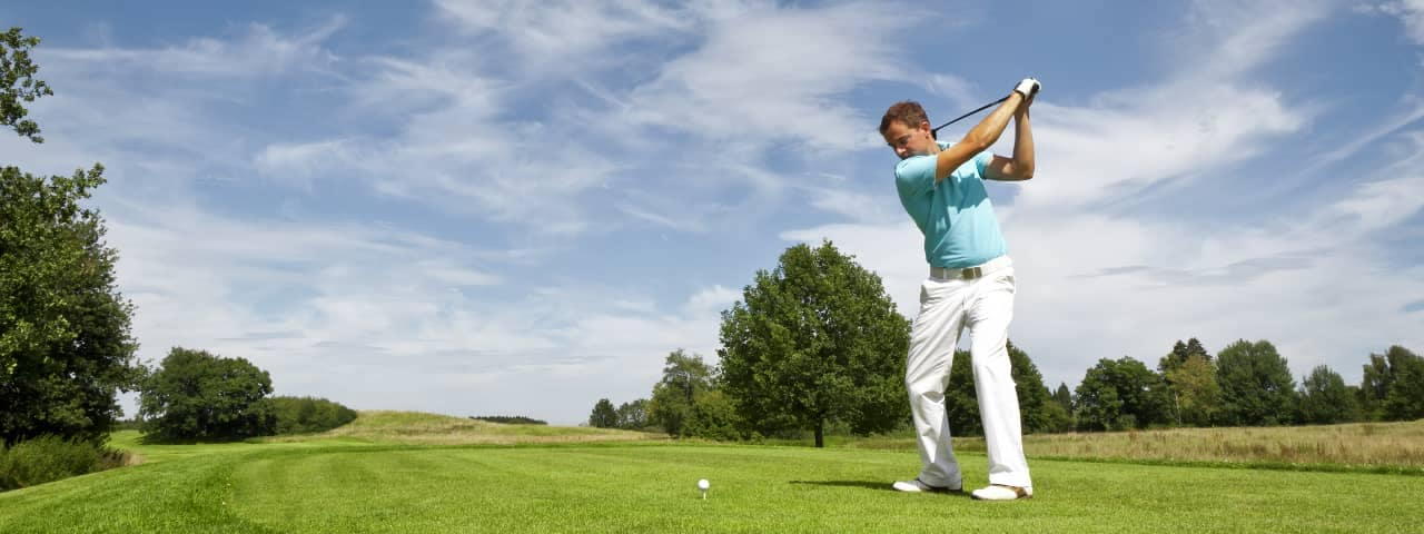 man plays golf on course