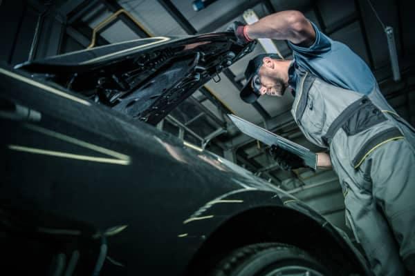 mechanic looks under car hood