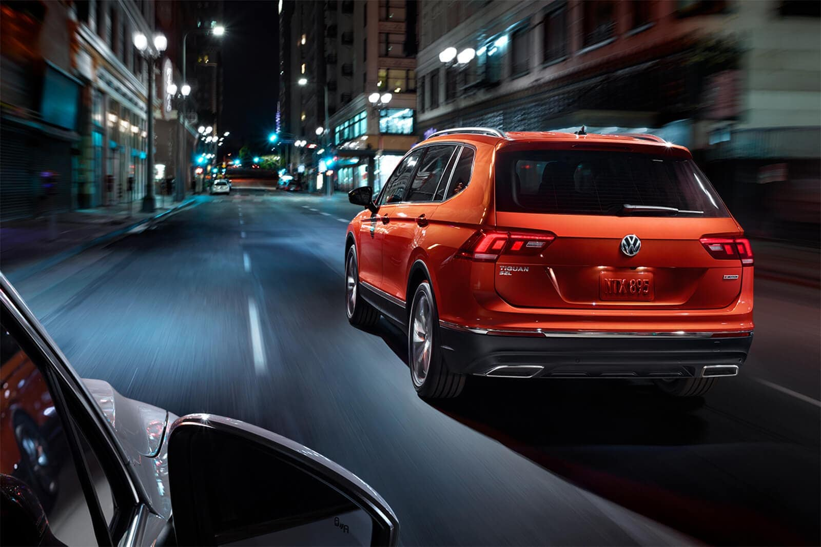2019 Volkswagen Tiguan in Habanero Orange Metallic driving down road
