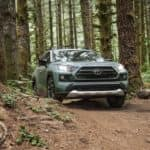 Front view of a 2020 RAV4 driving on a road through the woods