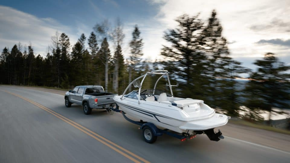 Silver Toyota Tacoma towing a boat along a highway